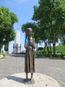 This commemoration statue is called Bitter Memory of Childhood and is located in Kyiv, it's part of a larger complex and museum that commemorates the Holodomor, the Memorial in Commemoration of Famines' Victims in Ukraine.  It was established in 2008, on the 75th anniversary of the Holodomor and sees around half a million visitors every year.  This scuplture is of a young girl, standing in a dress, verry thin, with very large eyes, she holds her hands against her chest and seem's to emot a question of why on her innocent face. She stands on what would have been used to grind wheat, a heavy circular disc that would be rolled in circles to crush wheat into flour.