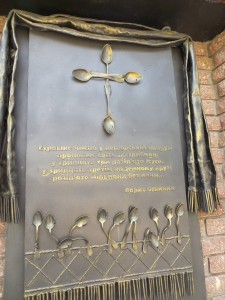 On either side of the center statue are plaques that are inscribed, this particular plaque has a cross created out of 4 brass spoons. Below is a poem written in Ukrainian, and below that are more spoons pointing up but bent out of shape.