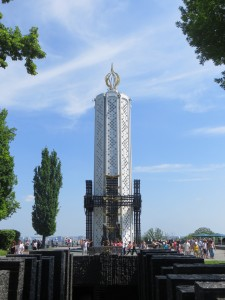 This is the dedicated Museum in Kyiv, the ground level of this museum looks like a single spire that has been made to look like a tall white candle, crowned with a gold metal flame, and at its base to 3/4's of the way up, crosses link all around it, almost embrace it in a circle . The museum itself is actually underground, built into the side of a hill.