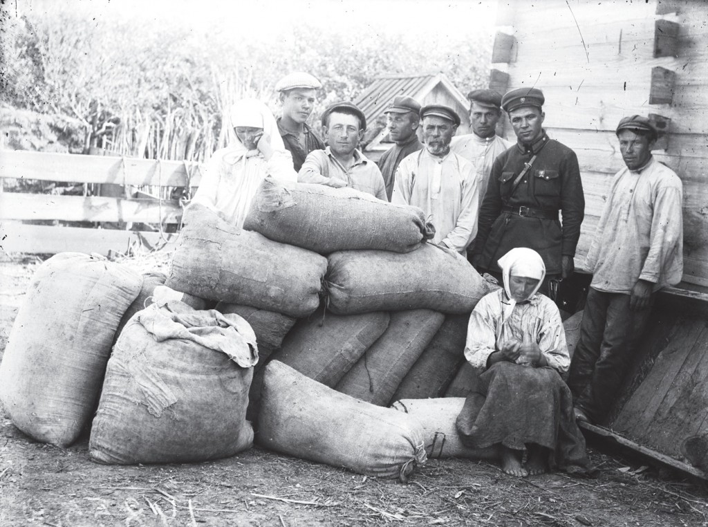 This is a black and white image taken in Donetsk in the 1932-33 and is part of the Innitzer collection. This image depicts 7 men standing behind sacks of grain, this grain will be packed up and taken away to store houses or shipped to other locations in Russia. In the front and beside the sacks of grain and two women, both who do not meet the gave or lens of the camera.