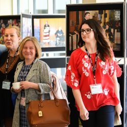Educators at the conference walking past a photo exhibit by Norbert Iwan