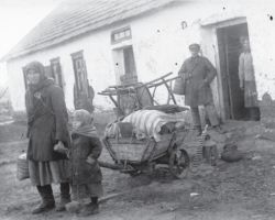 """Taken in Donetsk in 1932-33, this photograph shows a """"kulak"""" woman and her small child being evicted from their home in winter, dispossessed of everything but a small wagonload of their belongings pulled by hand behind them."""