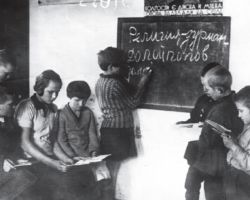 """Taken in Kharkiv in 1932-33, this staged photograph shows children in a classroom being indoctrinated. On the chalkboard, a child is writing """"Religion is a drug. Down with priests. Down with…"""" They are being taught that religious faith is unacceptable."""