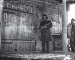 Taken in Kharkiv in 1932-33, this photograph shows a worker guarding stores of grain collected from the villagers. He holds a rifle at the ready to deter hungry villagers from approaching or trying to steal the grain.