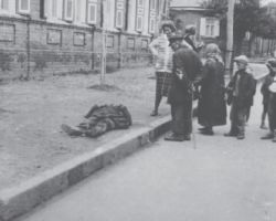 Taken in Kharkiv in 1933, this photograph is from the Innitzer Collection. It shows a man, who is near death, lying on the ground next to the street curb on the side of a busy street in the city. A small crowd has gathered to look at the body but do not seem to be helping him.