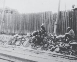 Taken in Kharkiv in 1933, this photograph is from the Innitzer Collection. It shows four starving orphan children sitting on a pile of rubble at the side of a road in rags.