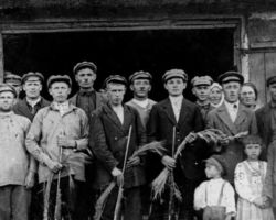 Taken in Kyiv in 1932-33, this staged photograph shows a group of villagers with three men in front holding rifles and stalks of grain. Standing beside them seem to be other villagers and a few children. The group is standing in front of a large set of open barn doors leading to a granary, where grain is stored.