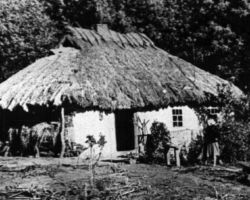Taken in Kyiv in 1932-33, this photograph shows a typical thatched roof village house with a woman standing nearby her garden.