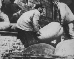 Taken in Kyiv in 1932-33, this photograph shows two men loading a single huge sack of grain onto a pile of similar grain sacks to be taken away via wagon.