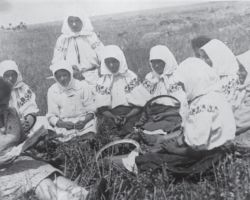 Taken in Vinnytsia in 1932-33, this photograph shows a staged representation of women on a collective farm, which is what Stalin wanted visitors of the USSR to see in Ukraine. Eleven women are sitting in a circle in a field wearing their embroidered shirts, which would never have been done because embroidered shirts were saved to be worn for very special occasions and traditions, not for sitting in a field.