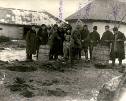 Taken in 1932-33, this photograph shows officials standing outside the house on a villager's property searching for hidden food stored in the ground. Using the long thin rods with a sharp end that two of the men are holding in the photograph, they would stick the rods into the ground where it seemed softer. If the rod pushed into the ground easily but was suddenly obstructed by anything hard, they would stop and dig in that area to find what had obstructed the rod. In this photograph, two barrels were found using this method and are being confiscated.