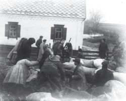 Taken in Donetsk in 1932-33, this photograph shows men dispossessing a kulak's home and removing its contents, packing them onto wagon carts. These possessions would be sold at an auction. Snow patches in the background show that it's still cold.