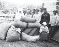 Taken in Donetsk in 1932-33, this Soviet staged photograph shows seven men standing behind sacks of grain which were hidden and are being confiscated. This grain will presumably be sent out of Ukraine to Russia or used for export. Sitting on a sack of grain in the foreground is the farmer with her head lowered gazing into her hands on her lap, awaiting punishment.