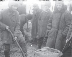Taken in Donetsk in 1932-33, this photograph shows several men looking on while standing around a sack that is being filled with the hidden grain by one man. In the background are some more men engaged in the same activity. All are wearing jackets and hats against the cold.