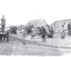 Taken in Donetsk in 1932-33, this photograph shows some men and women in front of some storage buildings in the village during collectivization. There are three wagons in the photo full of grain sacks ready to be delivered elsewhere.