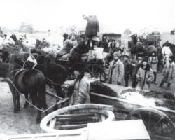 """Taken in Donetsk in 1932-33, this photograph shows officials confiscating everything that village leaders (""""kulaks"""") possessed – food, furs, grain, horses, and wagons."""